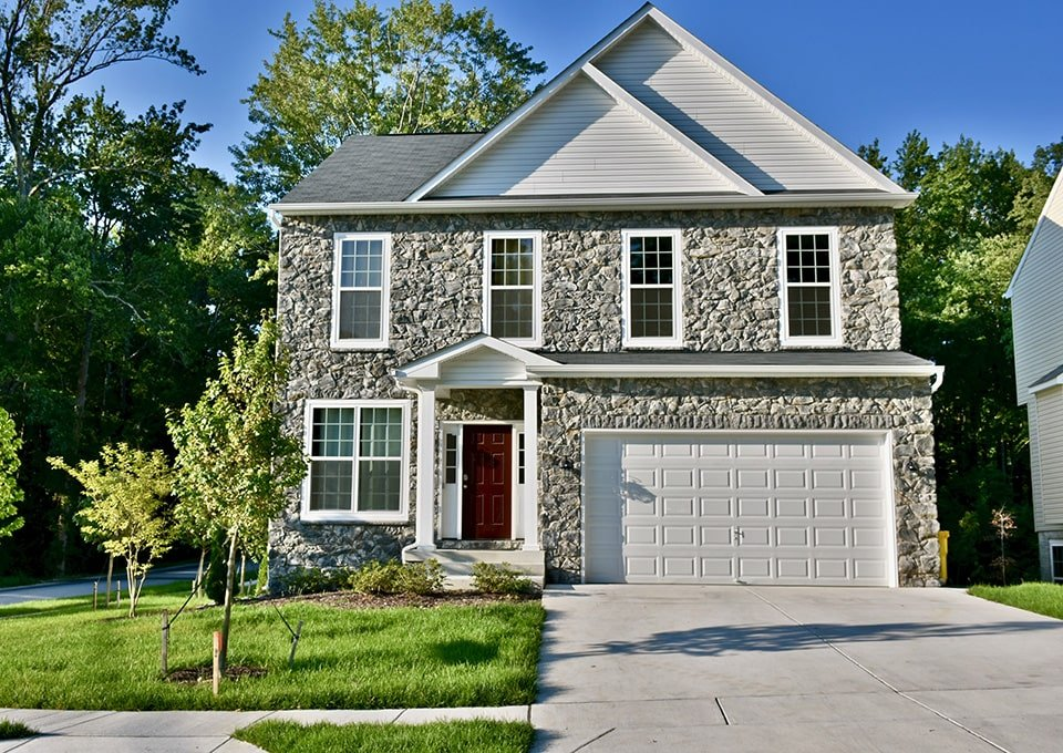 light grey and stone faced home with garage and red door