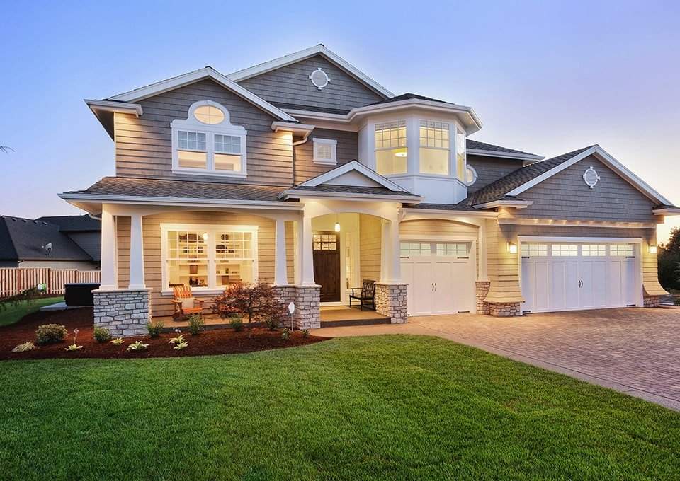 grey wood shingle home at dusk with lights on
